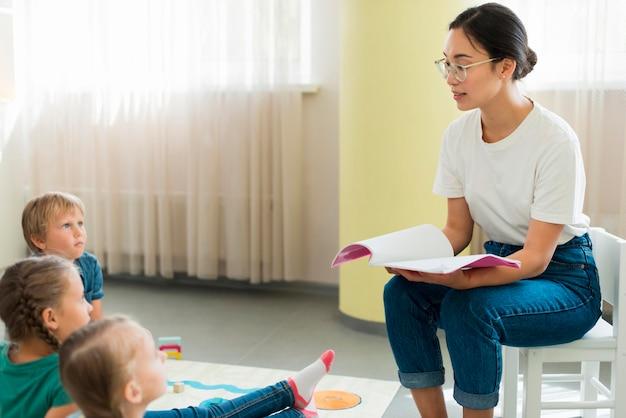 Maestra de vista lateral leyendo un cuento a sus alumnos