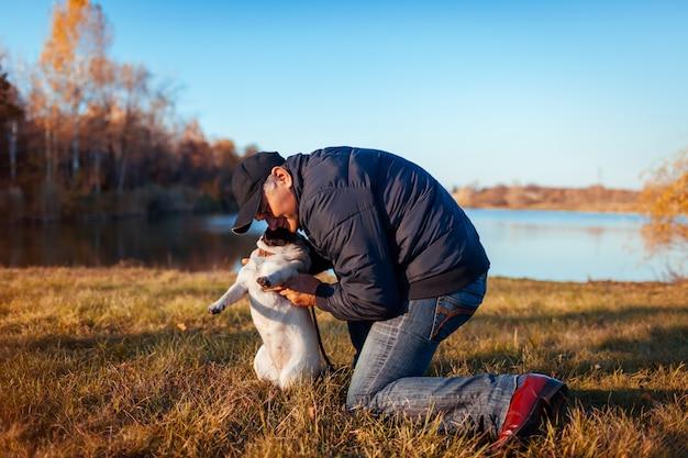 Maestro abrazando perro pug en otoño parque por río