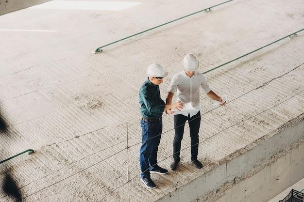 Maestro y arquitecto inspeccionando mirando el plano del edificio mientras inspecciona cómo va el trabajo.