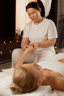 Maestro asiático de pelo oscuro. masajista profesional concentrada en uniforme blanco que se ocupa de las palmas durante un masaje complejo