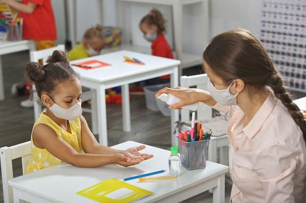 Un maestro ayuda a un estudiante afroamericano a desinfectar las manos en el aula.