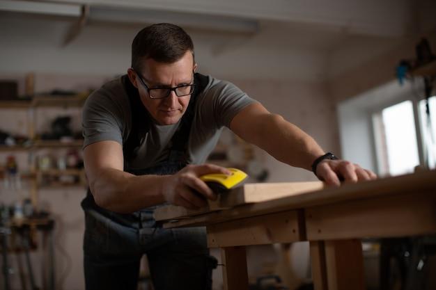 Maestro carpintero pieles pieza de madera.