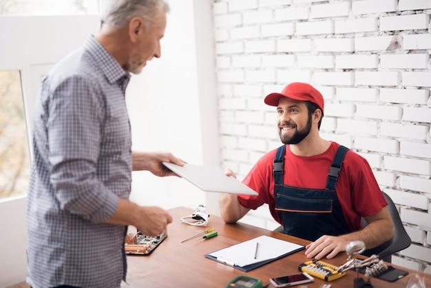 El maestro y el cliente acuerdan la reparación del dispositivo.