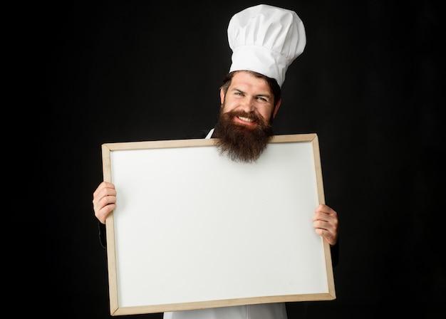 Maestro de cocina, panadero o cocinero con pizarra de menú. concepto de cocina, culinaria, publicidad y comida.