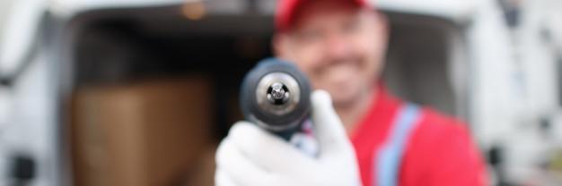 Maestro constructor masculino sonriente sosteniendo el taladro closeup