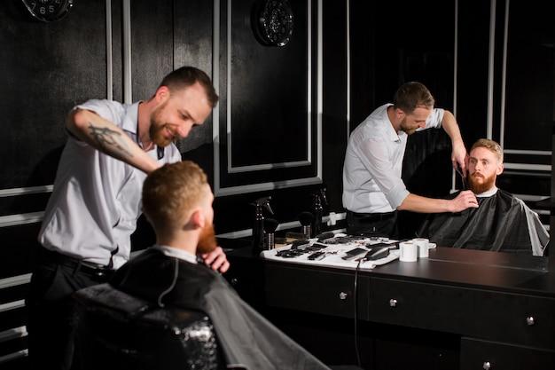 El maestro corta el cabello y la barba en la peluquería.