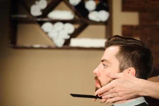Maestro corta el pelo y la barba de los hombres en la barbería