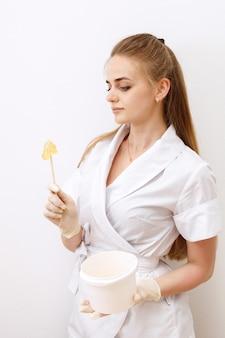 Maestro de depilación con pasta para shugaring sobre un fondo blanco.