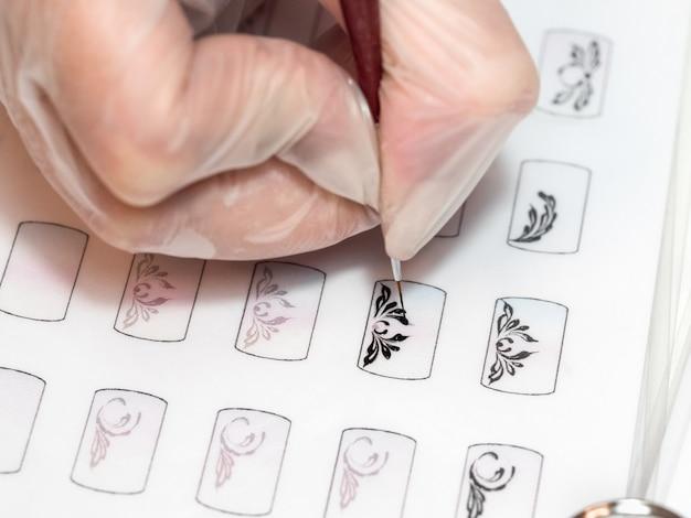El maestro dibuja un monograma. formación en pintura de monogramas para manicura. tarjetas de entrenamiento para manicura, de cerca.