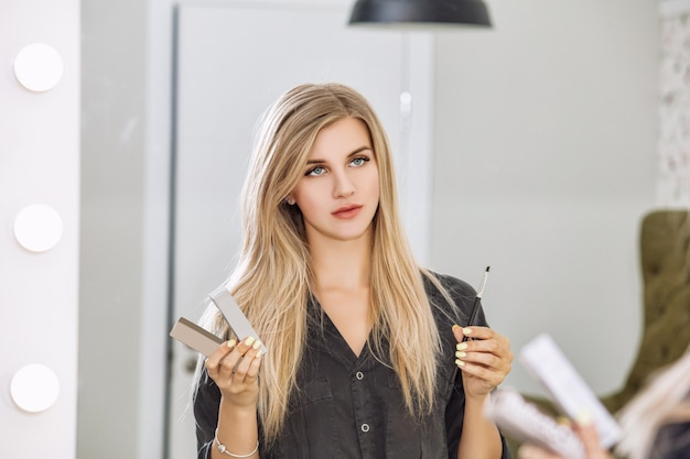 Maestro de diseño de cejas joven hermosa mujer con una sonrisa y herramientas profesionales en manos de un salón de belleza