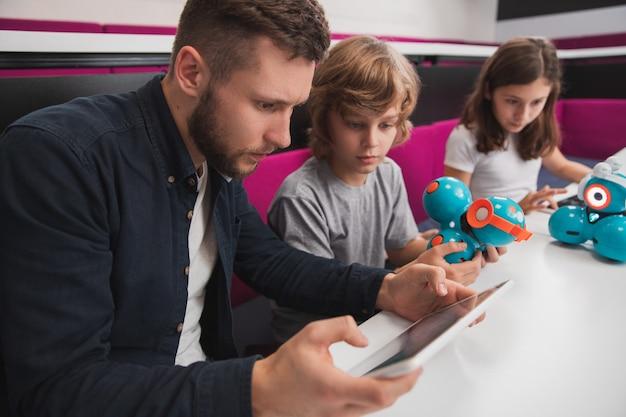 Maestro enfocado leyendo información en tableta mientras tiene una lección de robótica y crea robots con niños en la escuela