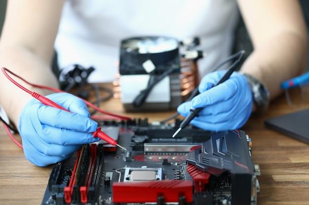 El maestro enguantado sostiene una sonda de microcircuito en sus manos.