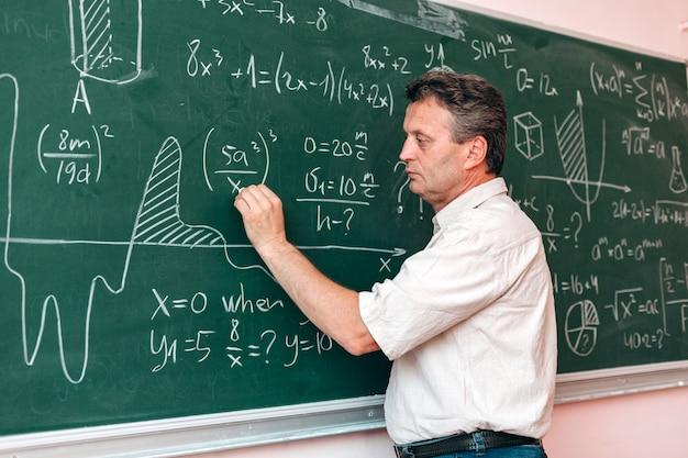 El maestro escribe en la pizarra y explica una lección.