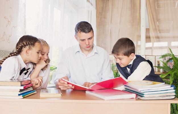 Un maestro en la escuela enseña a los niños a leerles un libro con atención