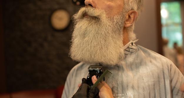 El maestro hace la corrección de la barba en el salón de peluquería. cerca de la foto.