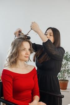 El maestro hace un peinado para una niña.