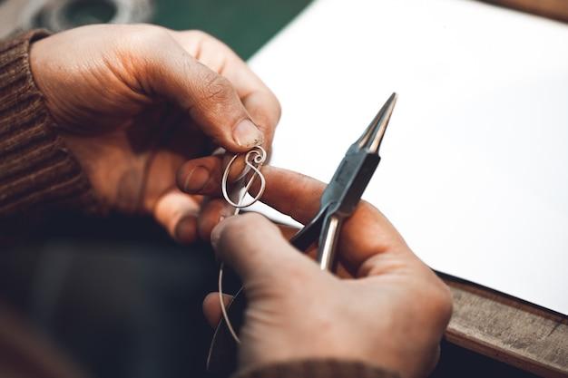 Maestro haciendo joyas con hilo metálico.