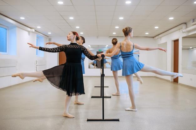 Maestro y jóvenes bailarinas se ejercitan en la barra en clase
