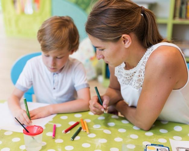 Maestro y niño con crayones de colores.