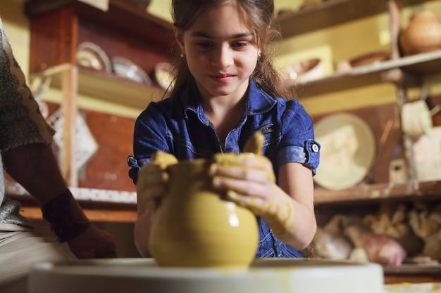 El maestro con el niño moldea una jarra de arcilla.
