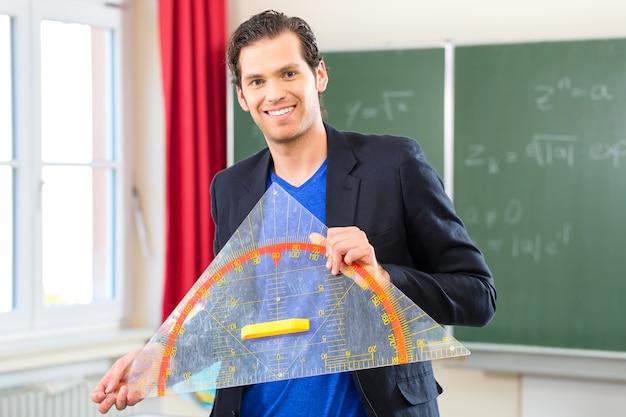 Maestro o docente en la escuela sosteniendo un triángulo de geometría frente a una pizarra en la clase de la escuela