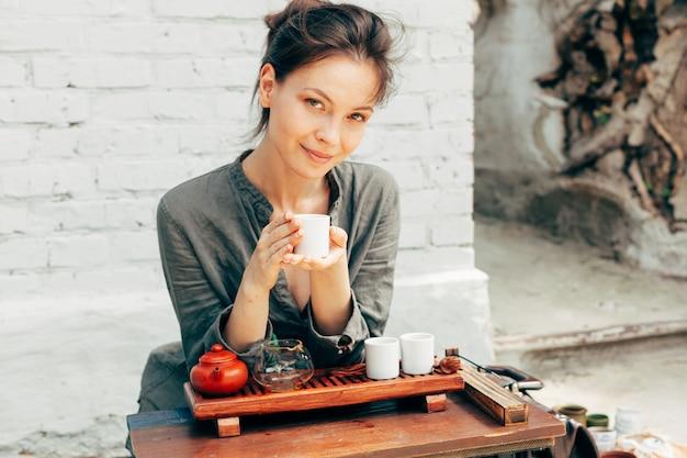 Maestro oriental de la ceremonia del té con pared de ladrillo blanco en el fondo.