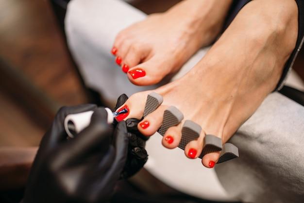 Maestro de pedicura en guantes negros cubren con esmalte de uñas de pie de clienta, vista de cerca