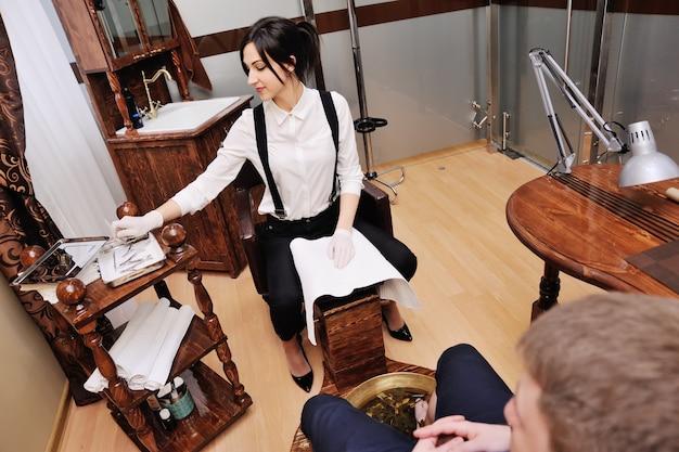 Maestro de pedicura que hace el cuidado de las uñas de los hombres del cliente sobre fondo de salón de spa
