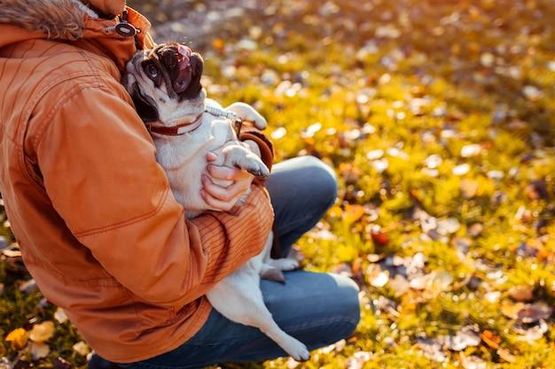 Maestro con perro pug en manos en el parque otoño