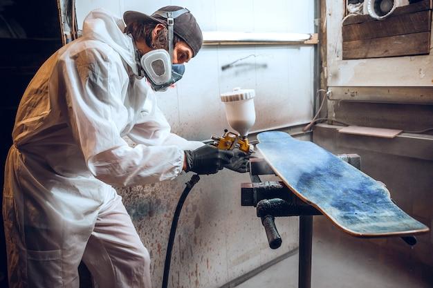 Maestro pintor en una fábrica - pintura industrial de madera con pistola