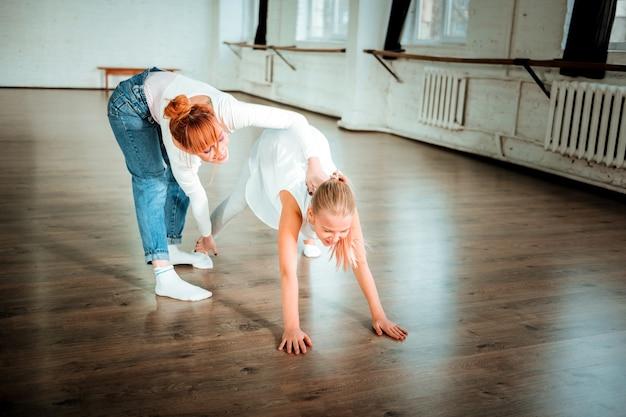 Maestro positivo. profesora de ballet hermosa delgada con cabello rojo sonriendo amablemente mientras trabaja con su estudiante