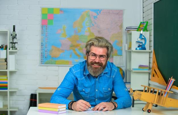 El maestro prepara lecciones en el aula de aprendizaje concepto de escuela de educación maestro masculino sentado en
