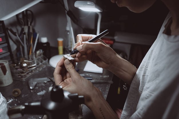 El maestro procesa el valioso metal en el taller casero.