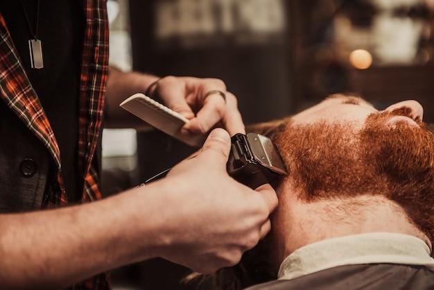 El maestro profesional de peluquería corta la barba del cliente.