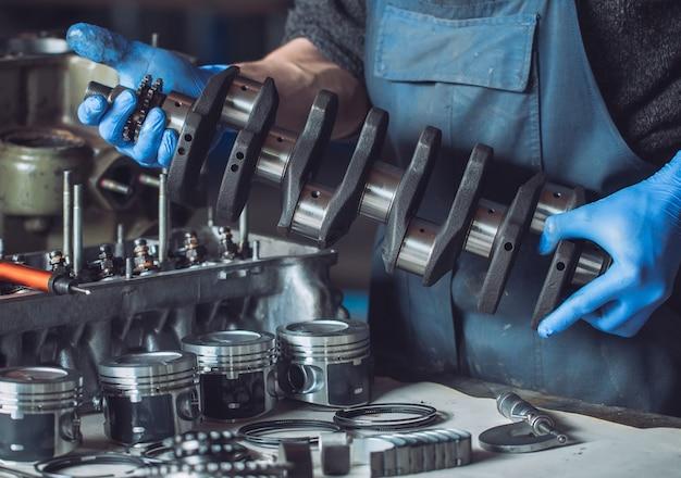 El maestro recoge un motor reconstruido para el automóvil.