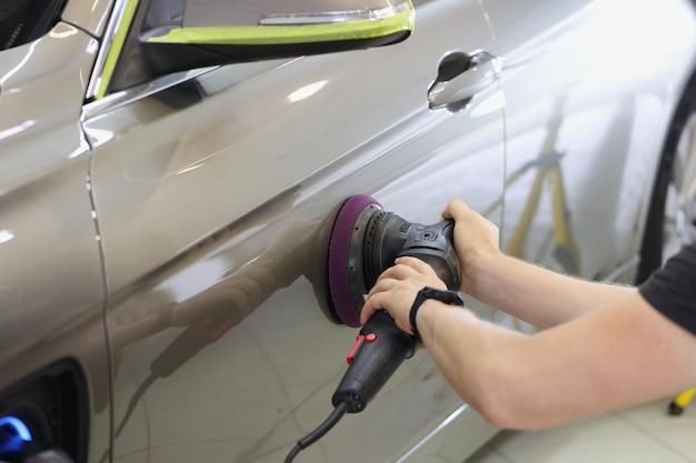 Maestro reparador pulido de la puerta del coche con una máquina especial en el taller y detalle de primer plano