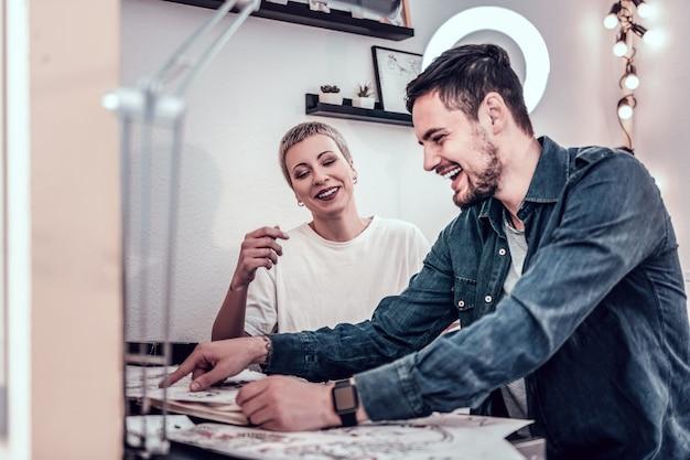 Maestro sentado cerca. maestra rubia de pelo corto que pasa tiempo con su cliente mientras observa diseños y se ríe