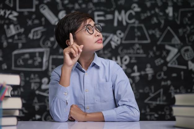 El maestro se sentó a pensar en enseñar en el aula.