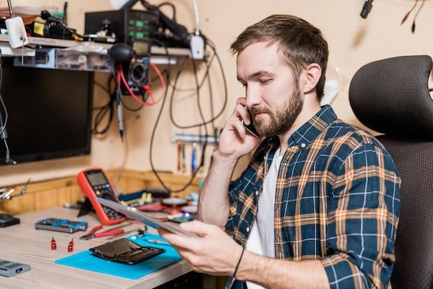 Maestro del servicio de reparación de dispositivos llamando a uno de los clientes mientras mira los datos en línea en el panel táctil