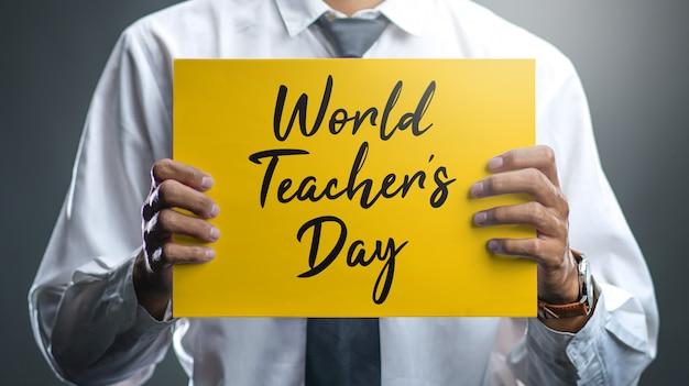 Un maestro sosteniendo un cartel del día mundial del maestro.