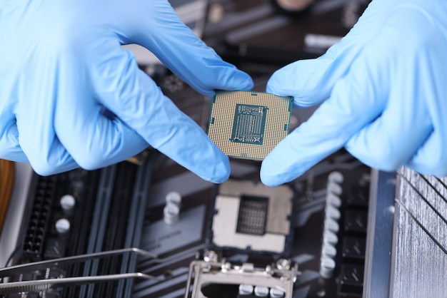 El maestro sostiene el microcircuito sobre las placas de la computadora. mantenimiento y servicio del concepto de equipo informático.