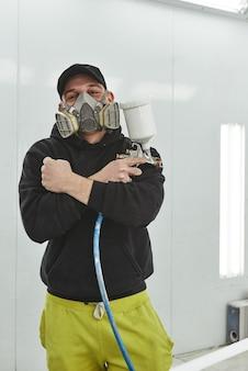 Maestro en su campo, el hombre sostiene un vaporizador con aerógrafo para pintar y teñir