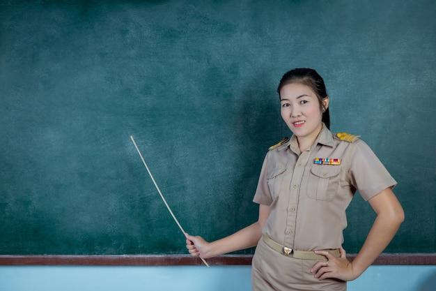 Maestro tailandés en traje oficial enseñando delante del tablero