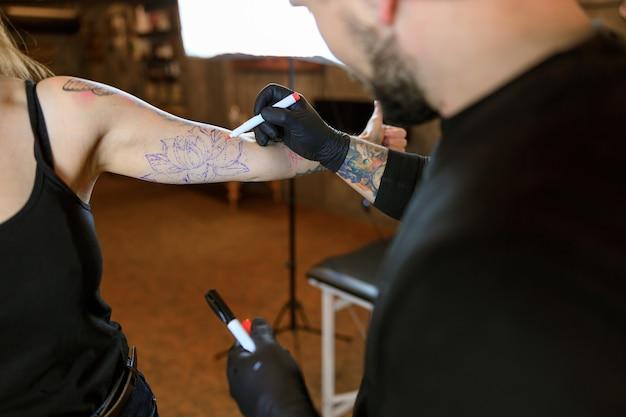Maestro del tatuaje caucásico barbudo masculino profesional está trabajando en un acogedor estudio atmosférico