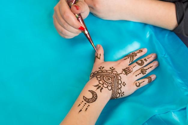 Maestro tatuando mehndi en mano de dama
