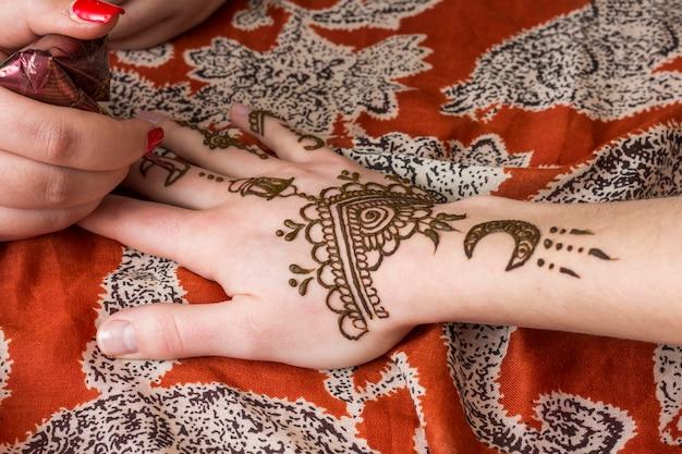 Maestro tatuando mehndi en mano de mujer