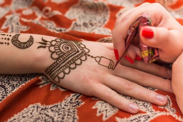 Maestro tatuando pintura mehndi en mano de mujer