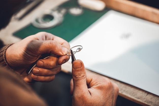 Maestro usando hilo metálico para hacer joyas