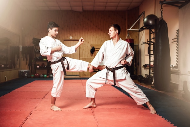Maestros de artes marciales en kimono blanco y cinturones negros, práctica de autodefensa en gimnasio