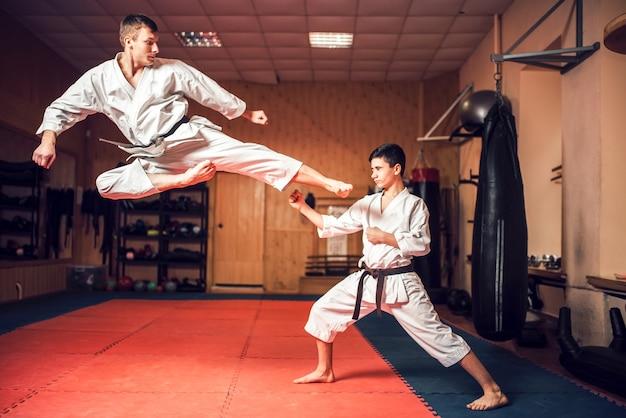 Maestros de artes marciales practican patada en salto